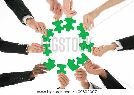 Business Team Joining Jigsaw Pieces In Huddle
