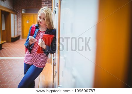 Pretty student with backpack leaning against the locker at the university