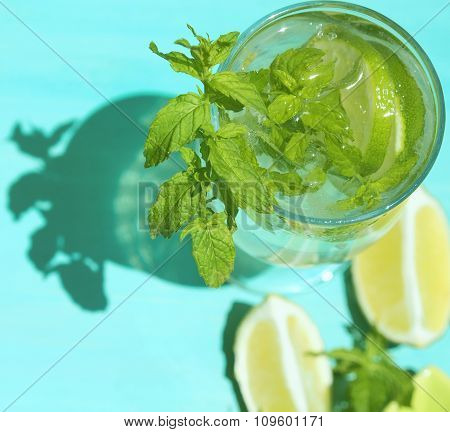 Mojito cocktail in the sun on green pastel