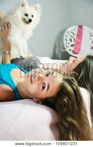 Two Girls Playingwith A Pomeranian On The Bed Close-up. Vertical