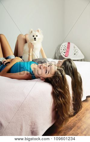 Two Girls Playing With A Pomeranian On The Bed. Vertical