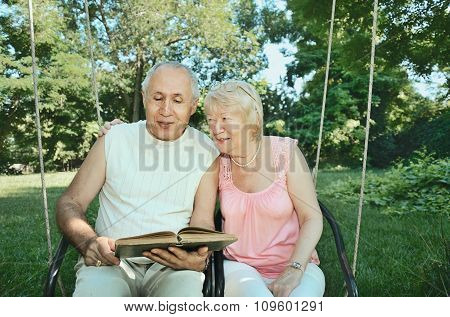 Smiling Elderly Man And  Woman 65-69 Years Old  Absorbedly Reading A Book In The Park