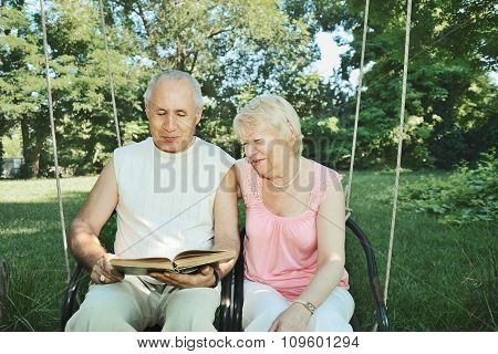 Smiling Mature Man And  Woman 65-69 Years Old Reading A Book In The Park