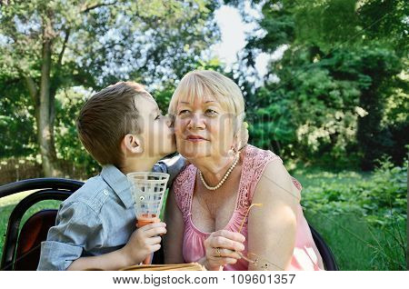 Grandson Hugs And Kisses On The Cheek His Grandmother. Tears In The Eyes Of His Grandmother's From H