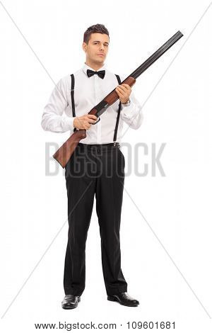Full length portrait of an armed young man holding a shotgun rifle and looking at the camera isolated on white background