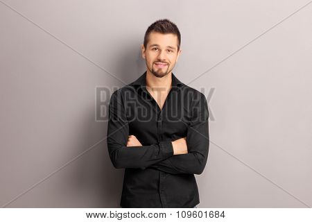 Handsome young man in a black shirt leaning against a gray wall and looking at the camera