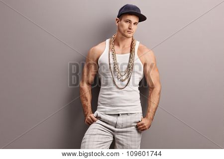 Young muscular rapper with a gold chain leaning against a gray wall and looking at the camera