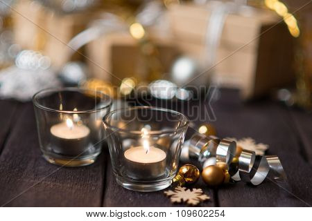 Christmas decoration with two burning candles and balls on a wooden table