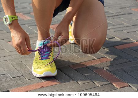 young fitness woman runner  tying shoelace before run