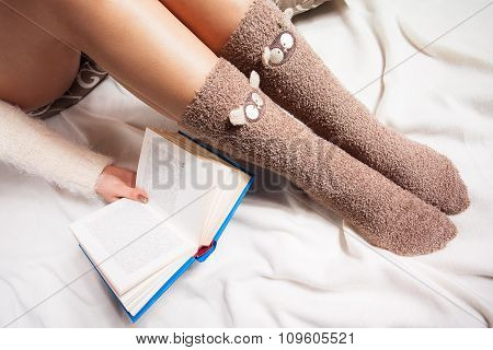 woman on the bed with old book