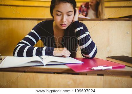 Focused student reading on notebook at the university