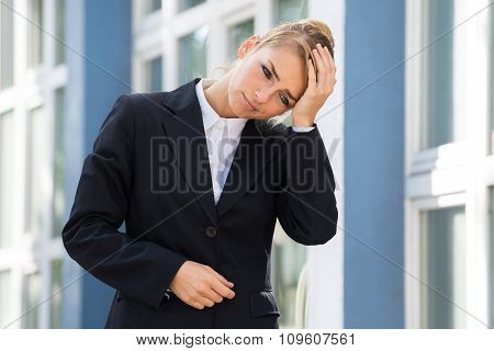 Sad Businesswoman Touching Head Against Buildings