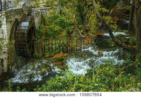 Autumn Landscape With A River And Water Wheel
