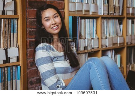 Smiling student sitting on the floor against wall in library at the university