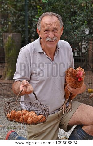 Happy farmer holding a brown hen and egg basket.