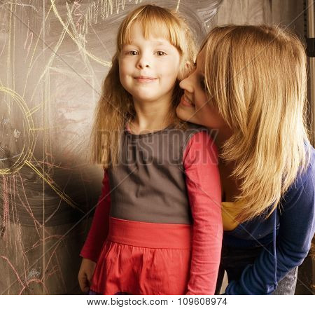 portrait of woman and little cute girl painting on blackboard