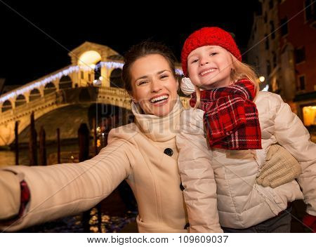 Mother And Daughter Taking Selfie Near Rialto Bridge In Venice