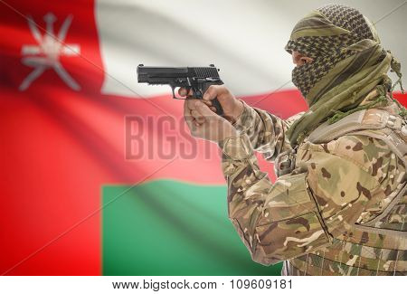 Male In Muslim Keffiyeh With Gun In Hand And National Flag On Background - Oman