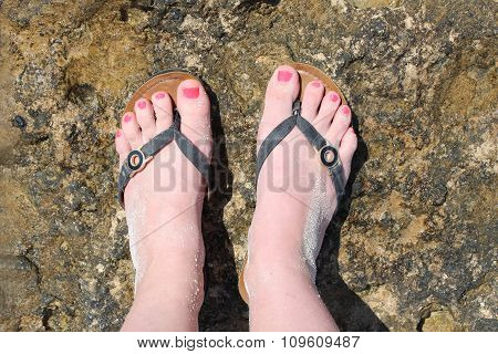 Beautiful foots of young woman wearing in flip flops, top view.