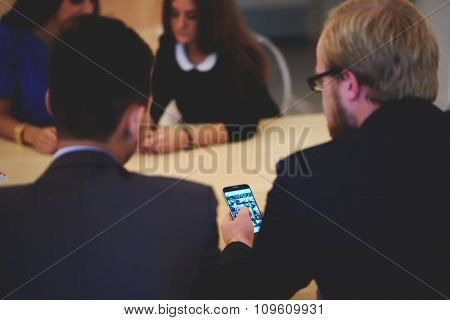 Young smart male office worker using cell telephone while sitting in modern interior