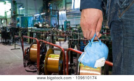 Worker with protective respirator at man hands at industrial factory