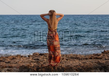 Young beautiful girl standing back and holding hands behind head.