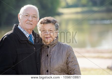 elderly couple with a lake in the background