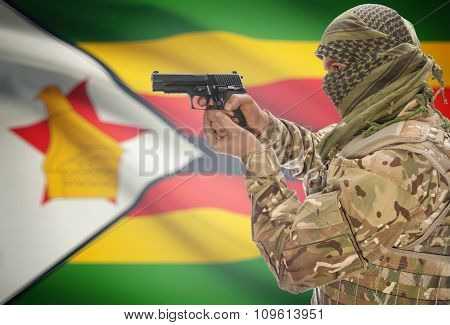 Male In Muslim Keffiyeh With Gun In Hand And National Flag On Background - Zimbabwe