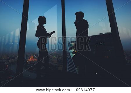 Silhouette of a two young business people standing in modern interior near big window