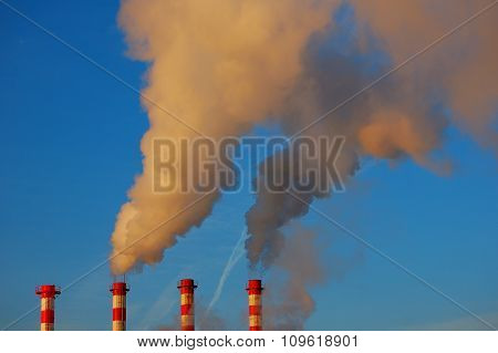 Factory Pipes Smoke In The Blue Sky