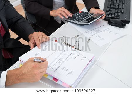 Close-up Of Two Businesspeople Calculating Invoice