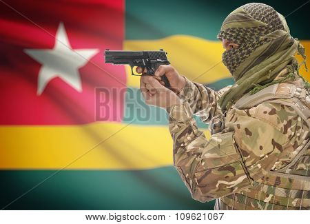 Male In Muslim Keffiyeh With Gun In Hand And National Flag On Background - Togo