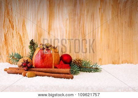 Baked apple with Christmas decoration on a wooden background.