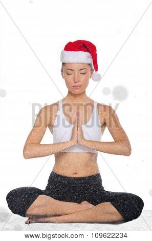 Concentrated Asian Woman In Christmas Hat With Snow Practicing Yoga