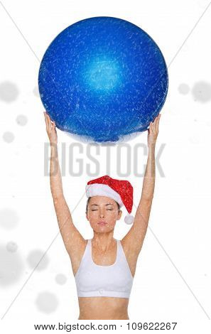 Asian Woman In Santa Cap Holds Fitball Under Snow