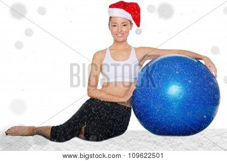 Happy Asian Woman In Christmas Cap With Fitball Under Snow