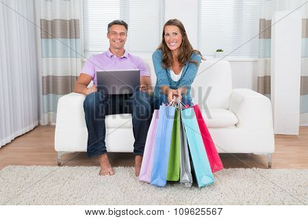 Mature Couple With Laptop And Shopping Bags