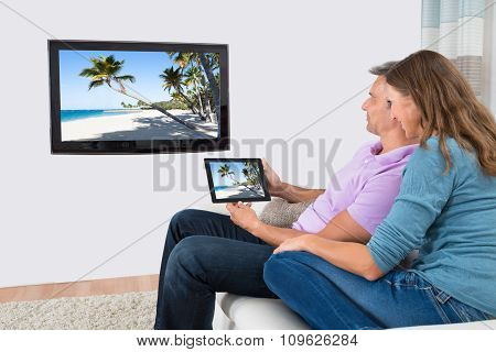 Couple Using Digital Tablet For Watching Television