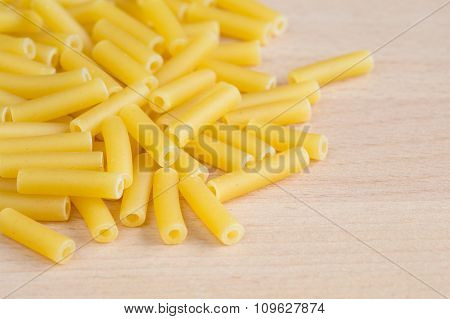 Macaroni pasta on a wooden chopping board