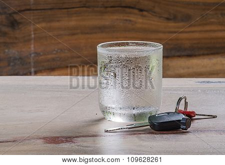 Glass Cold Water,car Key On Wooden Floor.