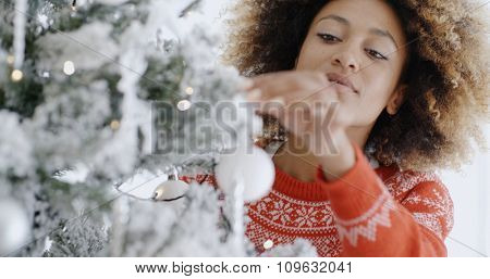 Pretty young African woman decorating a Christmas tree hanging ornaments on its branches  close up focus to her face