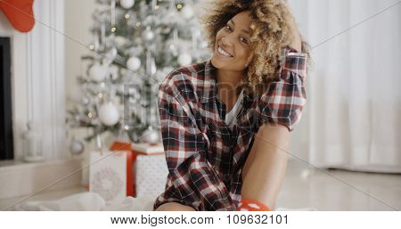 Thoughtful trendy young African woman sitting on the floor in front of a decorated Christmas tree at home looking at the camera