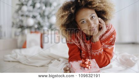 Thoughtful attractive young African woman with a Christmas gift lying on the floor in the living room in front of the decorated tree
