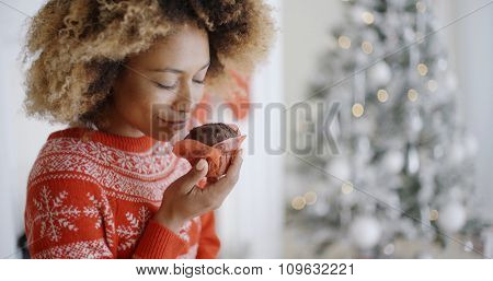 Young African woman savoring a freshly baked spicy Christmas cake that she is holding in her hands in front of the Christmas tree