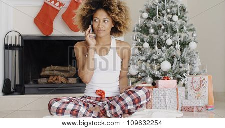 Attractive trendy young African woman phoning her friends or family at Christmas sitting in front of the decorated tree chatting on her mobile phone