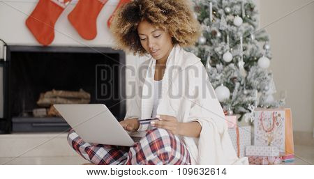 Pretty young woman buying Christmas gifts online using her credit card on a laptop computer as she sits on the floor in front of the decorated tree.