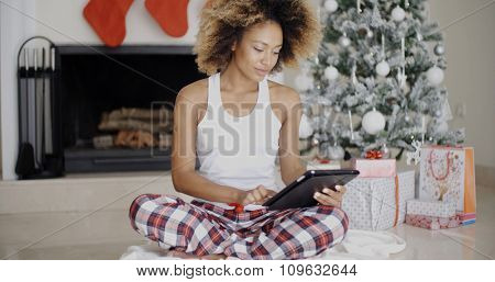 Thoughtful young woman catching up on Christmas news as she sits on the floor in front of the decorated Christmas tree in her living room reading the screen on her tablet computer.