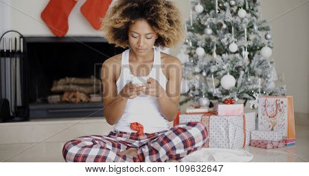 Young woman sending a Christmas text message on her mobile phone as she sits on the floor in front of the decorated hearth and Xmas tree.