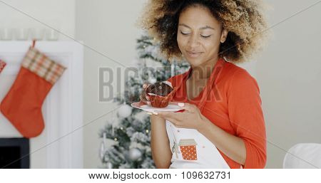 Happy young African woman celebrating Christmas looking with pleasure at a freshly baked cake in her hands as she stands in front of the decorated tree.
