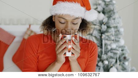 Young woman wearing a Santa hat standing in front of a decorated tree in her living room enjoying a festive red mug hot coffee at Christmas.